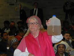 A Flint Michigan Resident displays the tan colored water received our of her home water faucet.